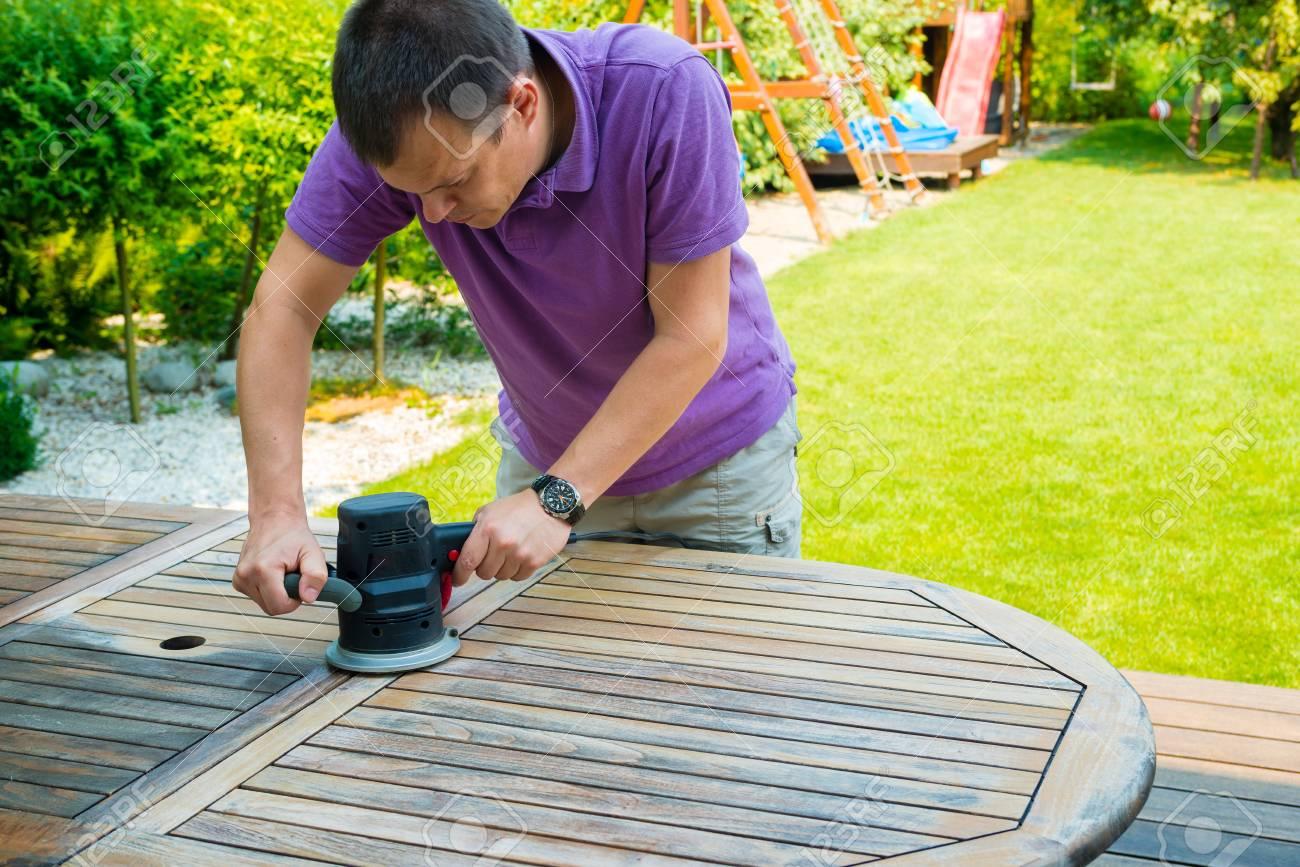 Jeune homme - charpentier travaillant avec ponceuse électrique dans le  jardin - polissage ancienne couleur de la table en bois