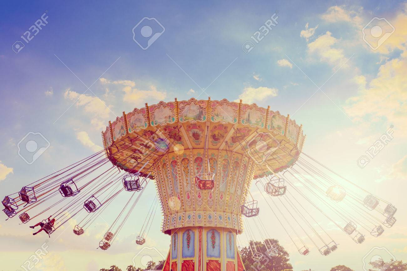 Wave Swinger ride against blue sky, vintage filter effects - a swinging carousel fair ride at dusk - 86187361