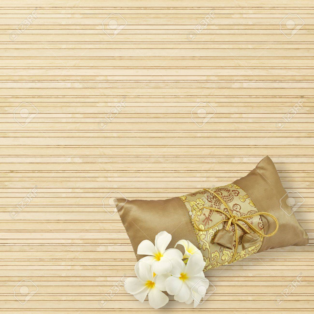 Tradition gold silk pillow and plumeria flowers isolated on bamboo stock photo tradition gold silk pillow and plumeria flowers isolated on bamboo mat background mightylinksfo