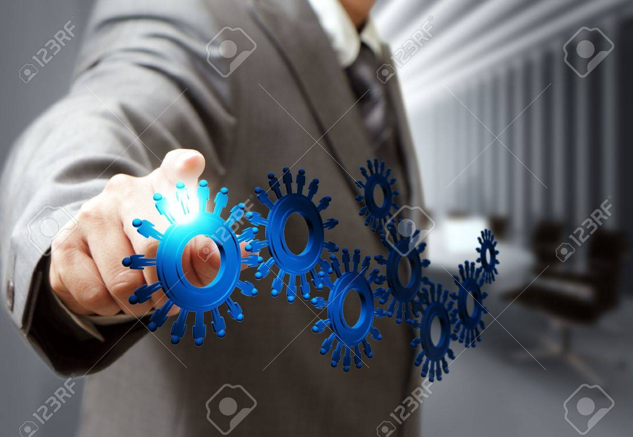 business man hand point cogs icons in board room Stock Photo - 16080939
