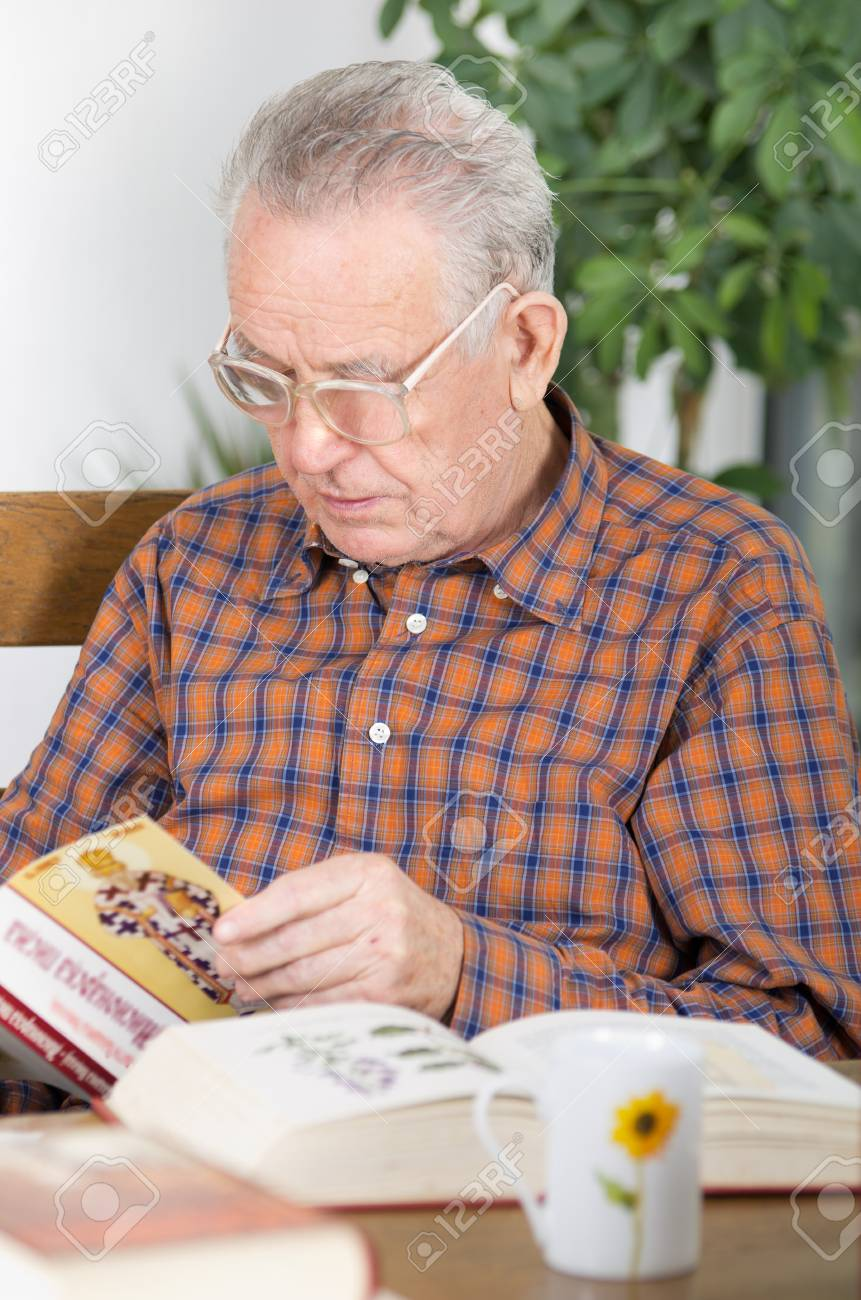 Old Man With Reading Glasses Reading Book In Dining Room Stock Photo,  Picture And Royalty Free Image. Image 25797350.