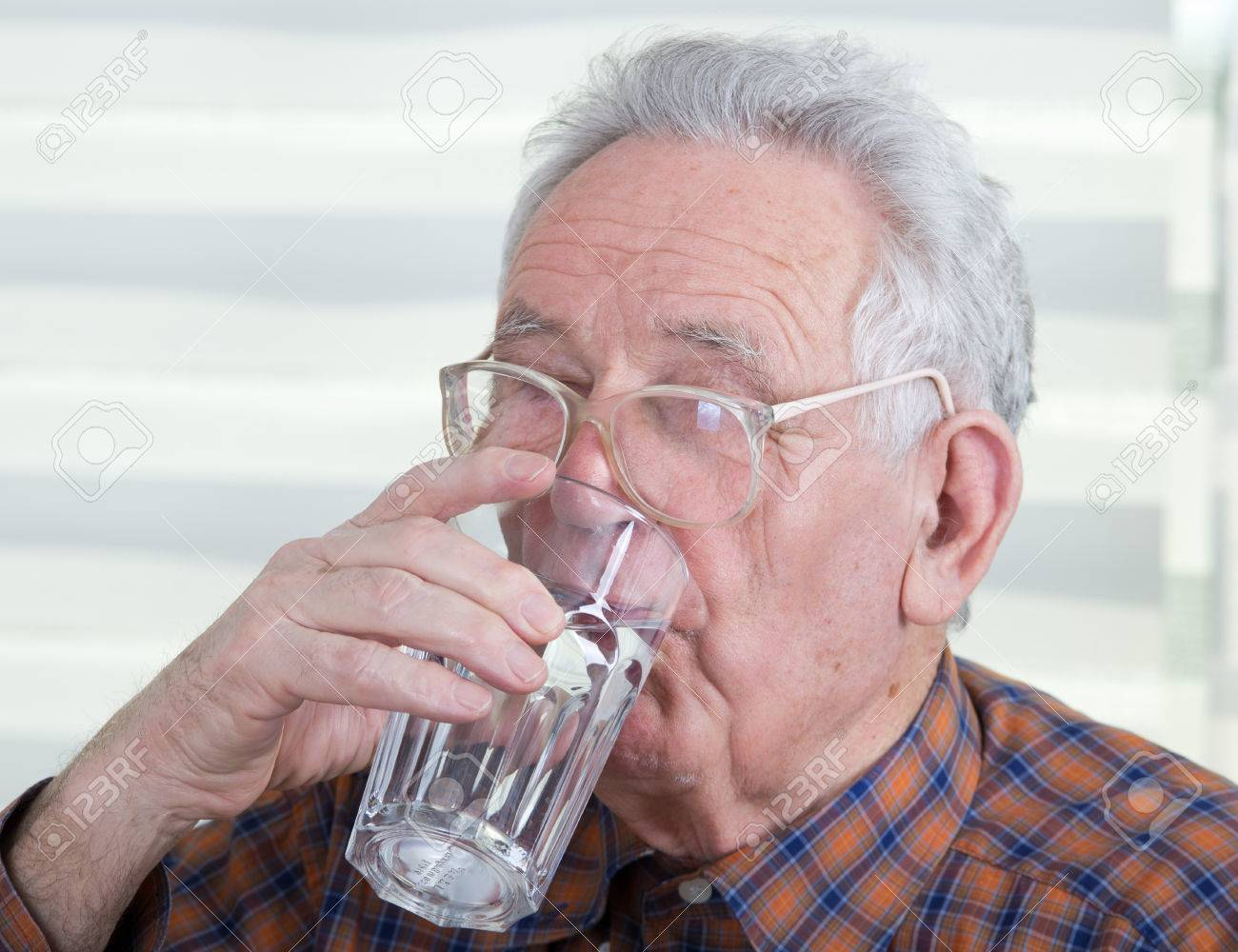 Old Man With Reading Glasses Holds And Drinks Glass Of Water Stock Photo,  Picture And Royalty Free Image. Image 25893196.