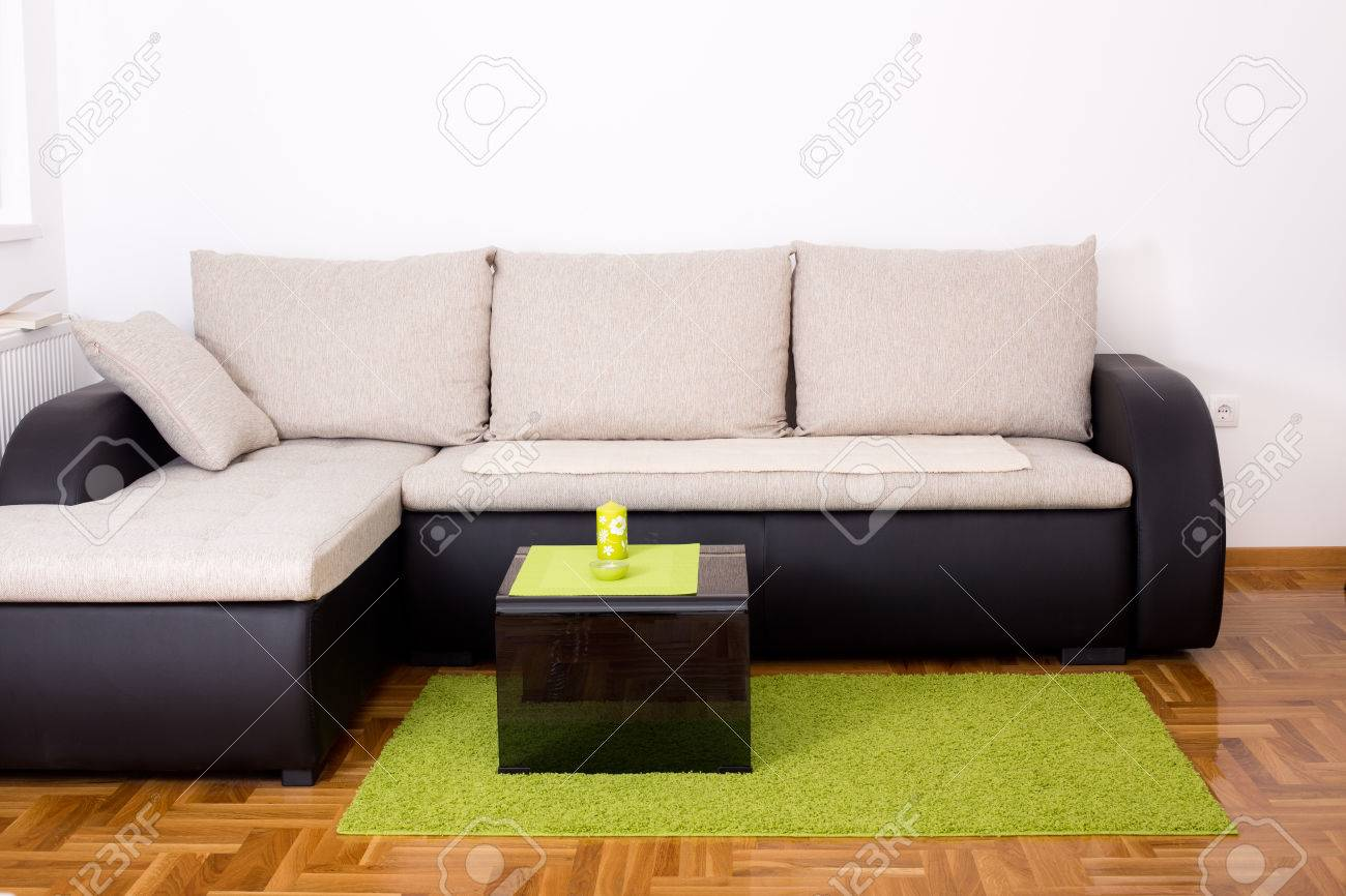 Elegant Small Sofa In The Corner Of Living Room With Black Glass