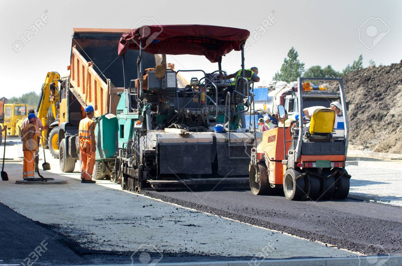 paving machine loaded with fresh asphalt laying finish layer at the road stock photo 46223440