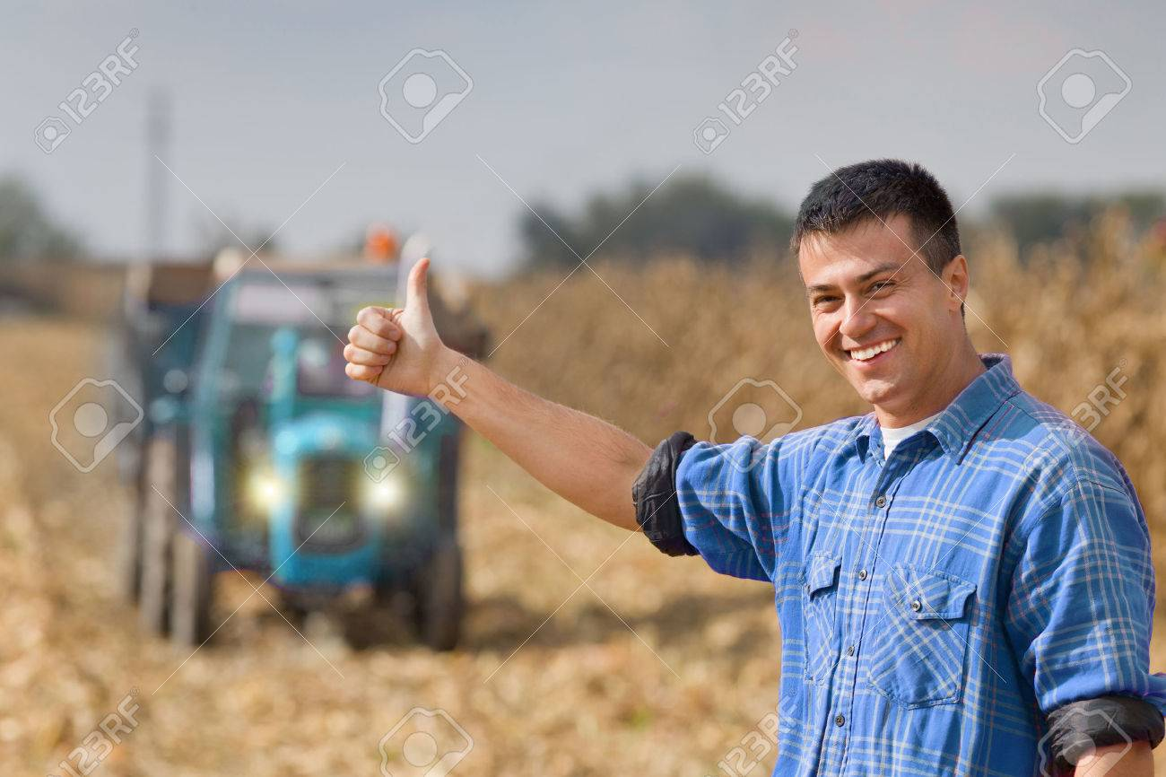 Young smiling farmer showing thumb up as ok sign on farmland. Tractor with trailer in background - 49205422