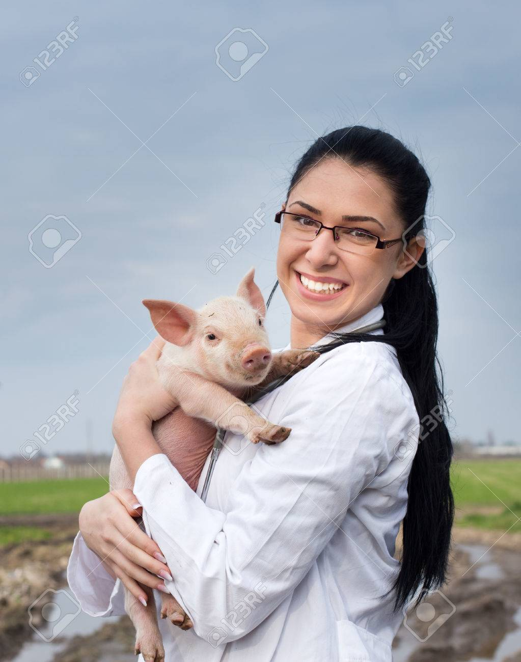 Happy young veterinarian girl holding cute piglet in her arms on the farm - 53744914