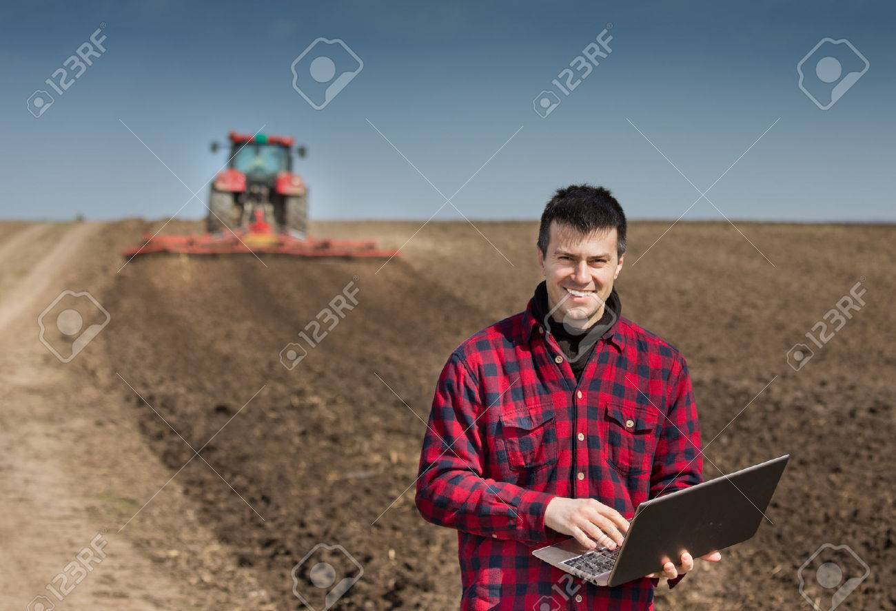 Young farmer with laptop supervising work on farmland, tractor harrowing in background - 53966474