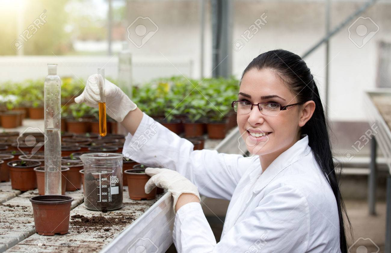 Young woman biologist in white coat holding test tube with orange chemistry in front of sprouts in flower pots - 57944454