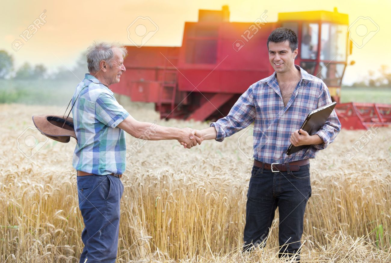 Two farmers shaking hands on wheat field while combine harvesting behind - 59605842