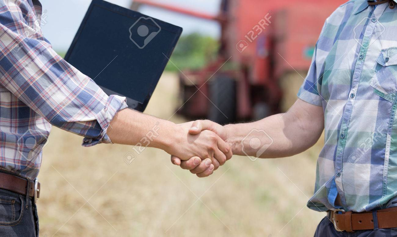Close up of two men in plaid shirts shaking hands on the farmland. Combine harvester working in background - 61492793