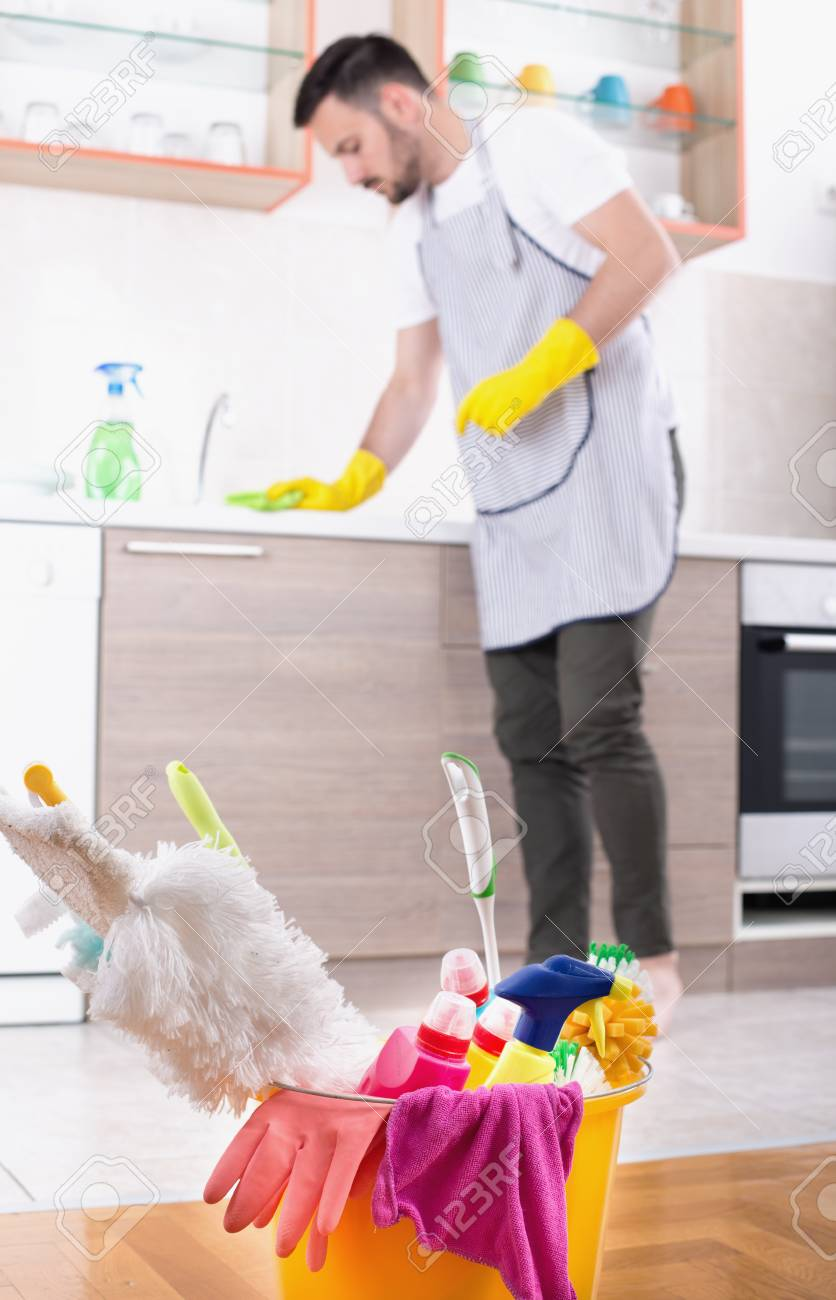 Close Up Of Bucket Full Of Cleaning Products And Equipment And Man With  Apron Wiping Kitchen