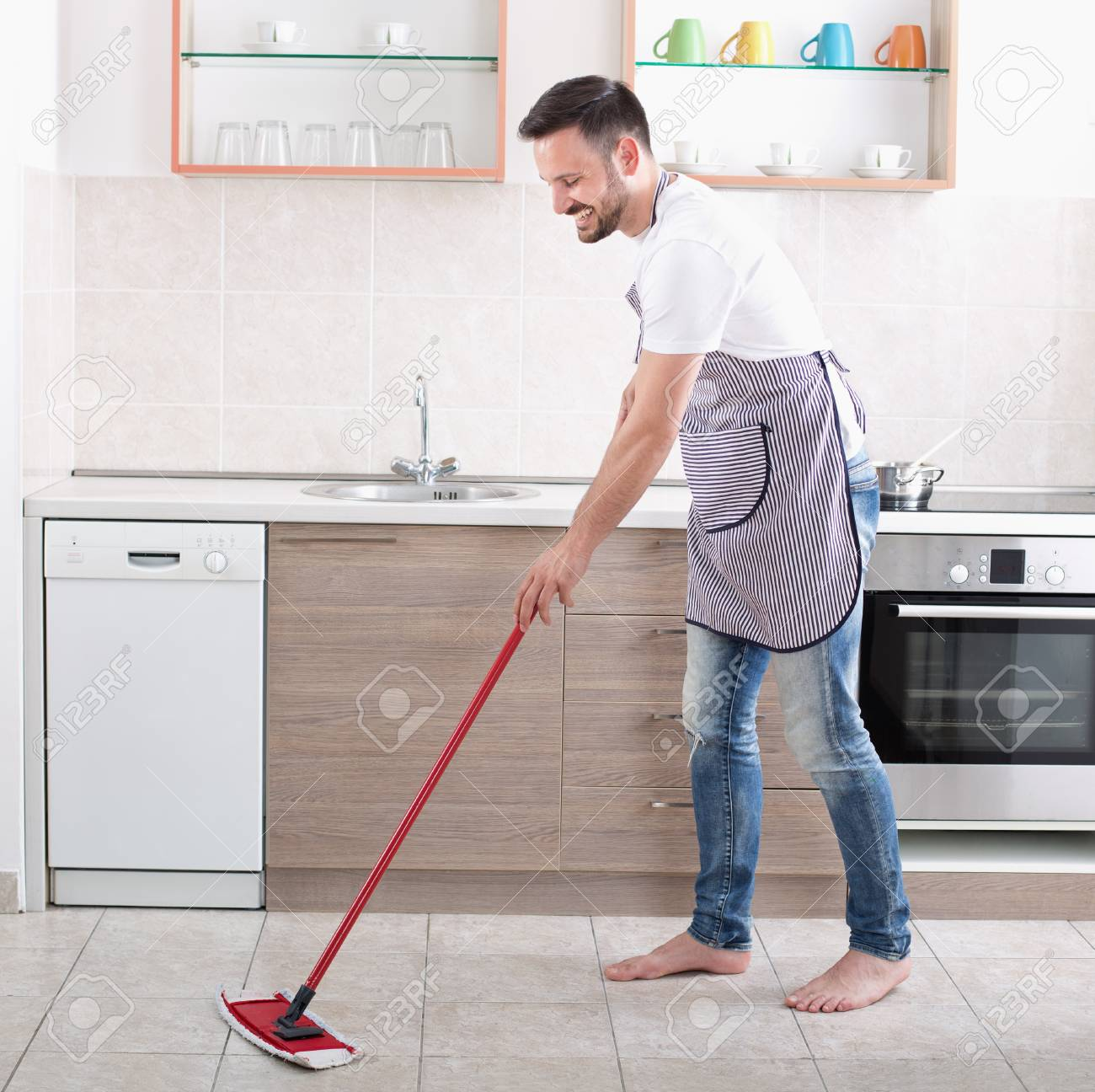 Young handsome man mopping tiled floor in kitchen husband housework stock photo young handsome man mopping tiled floor in kitchen husband housework concept dailygadgetfo Image collections