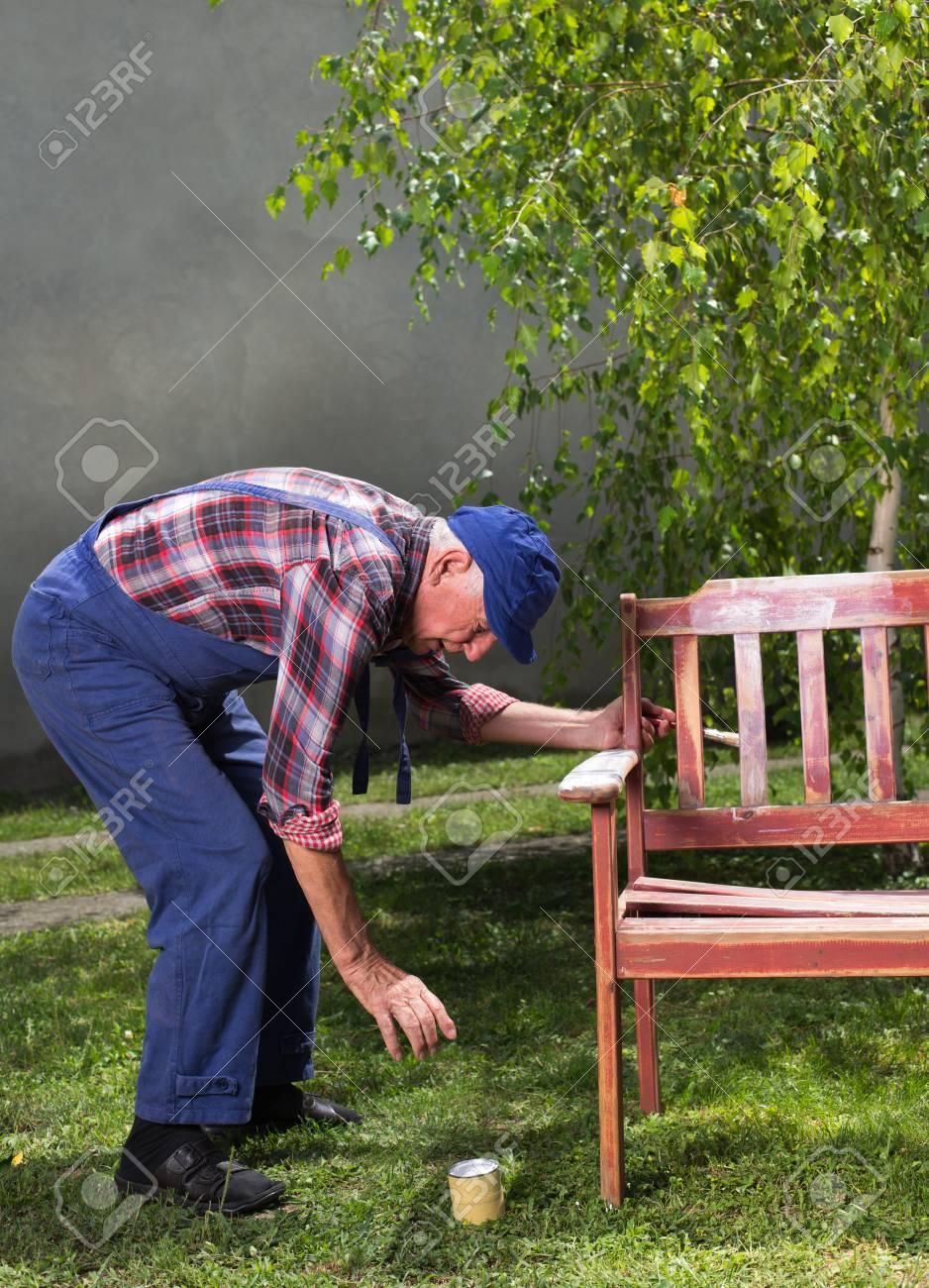 Peindre Les Meubles Anciens senior homme en salopettes peinture vieux banc dans le jardin après le  sablage. réparation de meubles anciens