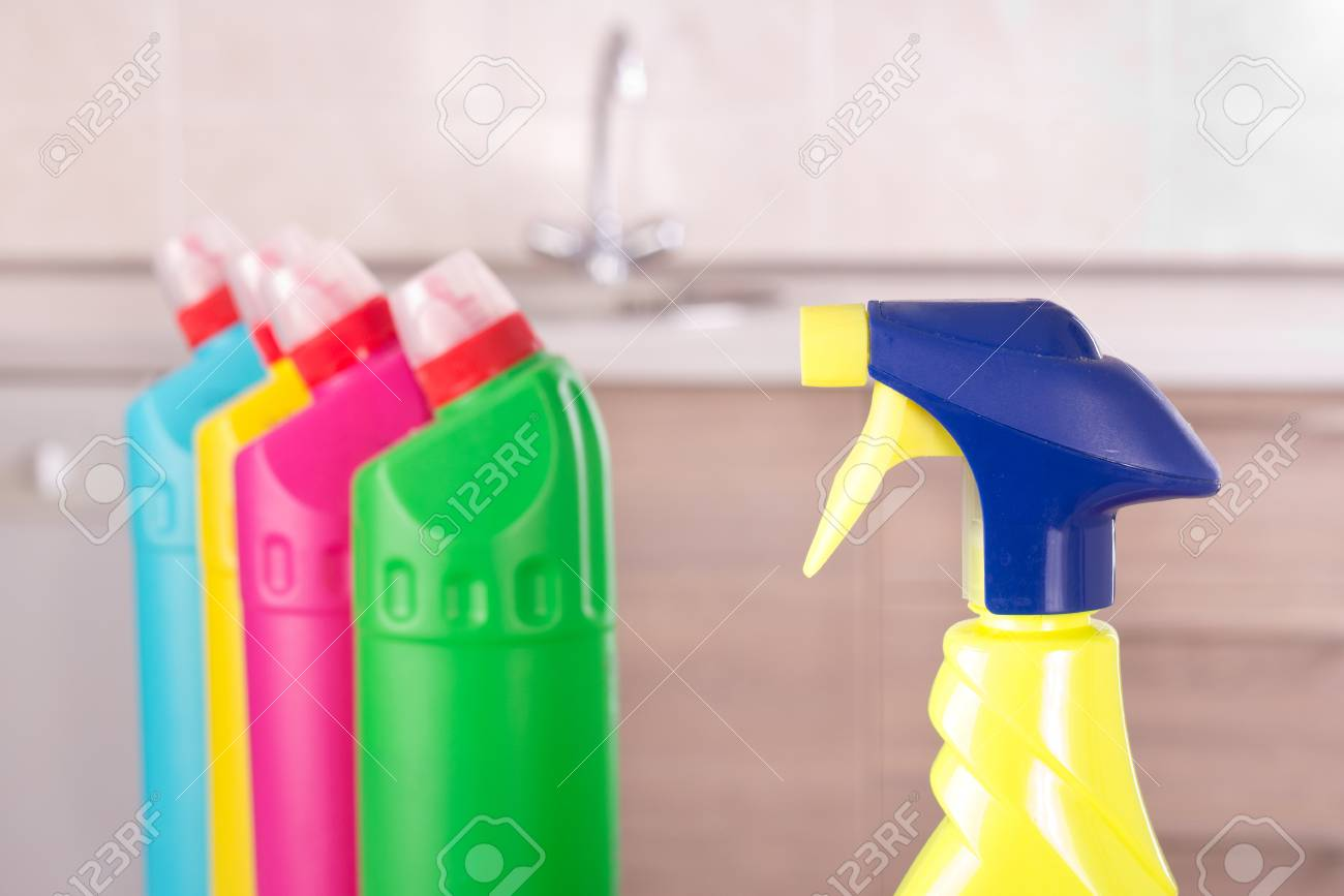 Close Up Of Spray Bottle With Different Cleaning Products In Background On  Kitchen Table. Housekeeping