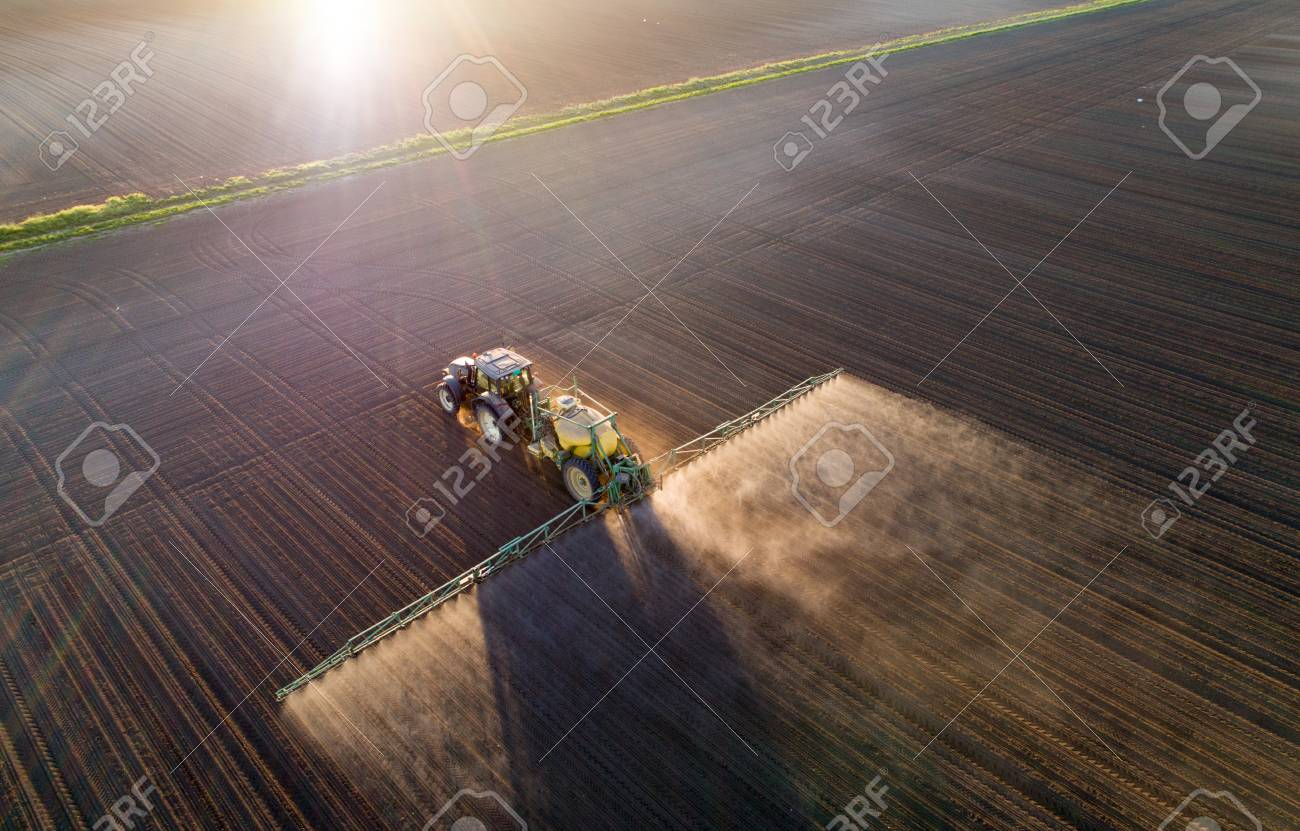 Aerial image of tractor spraying soil and young crop in springtime in field - 101101809