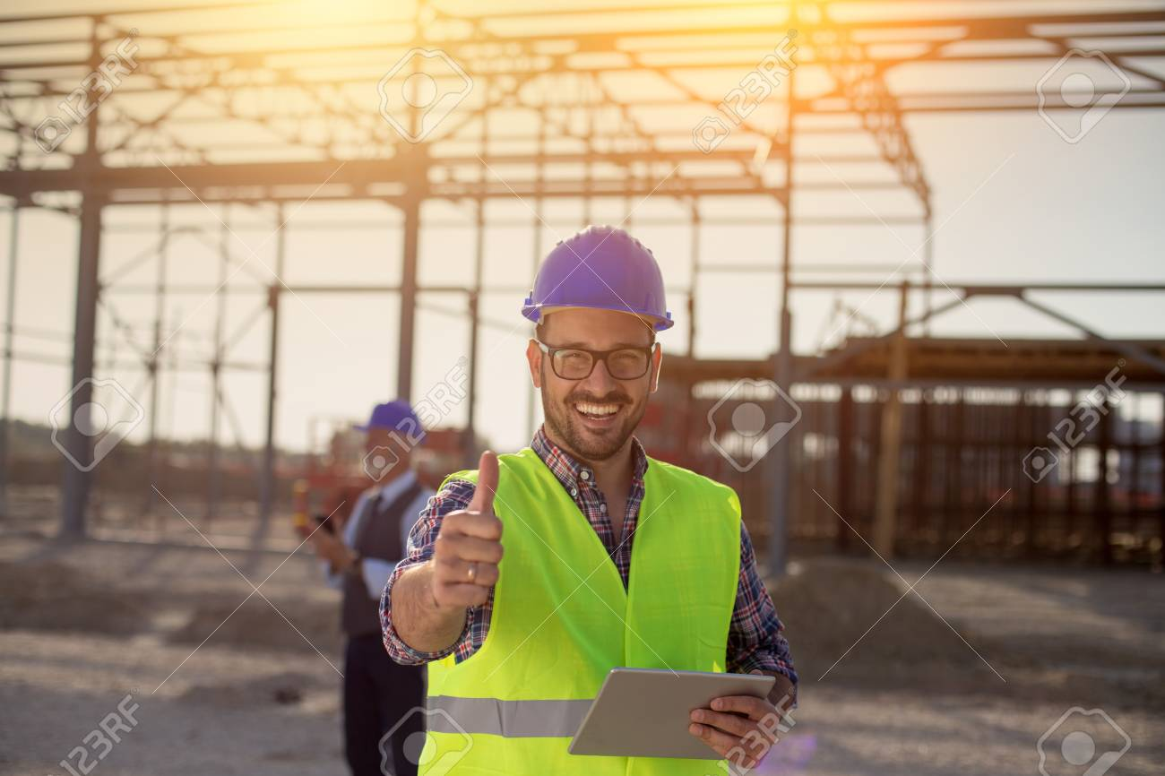 Portrait of satisfied engineer holding tablet and showing thumb up on building site - 115960818