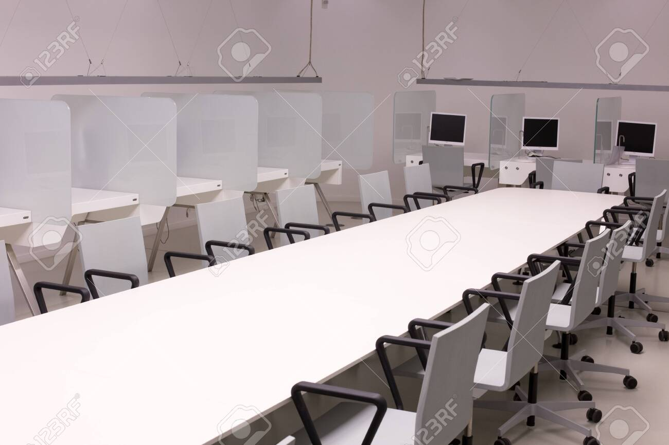 Modern computer lab with white furniture and suspended lighting