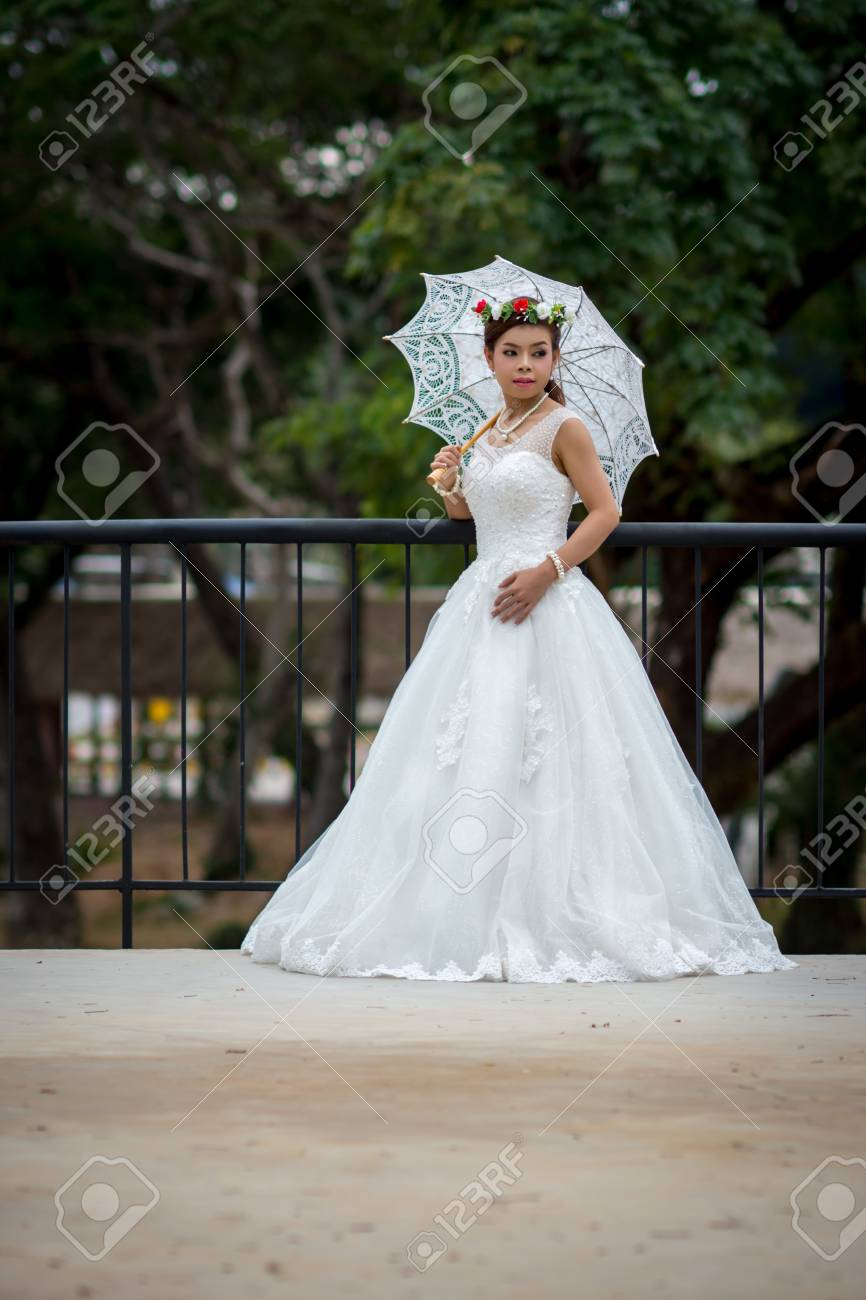 018ac10449e Stock Photo - Young girl in a bridal gown holding a white umbrella on a steel  bridge.
