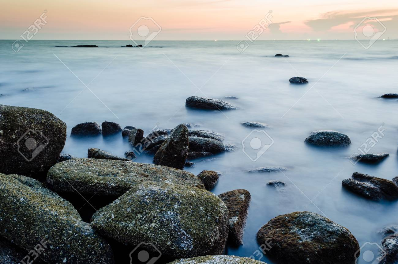 Wave and the rock with sunset sky Stock Photo - 18692142