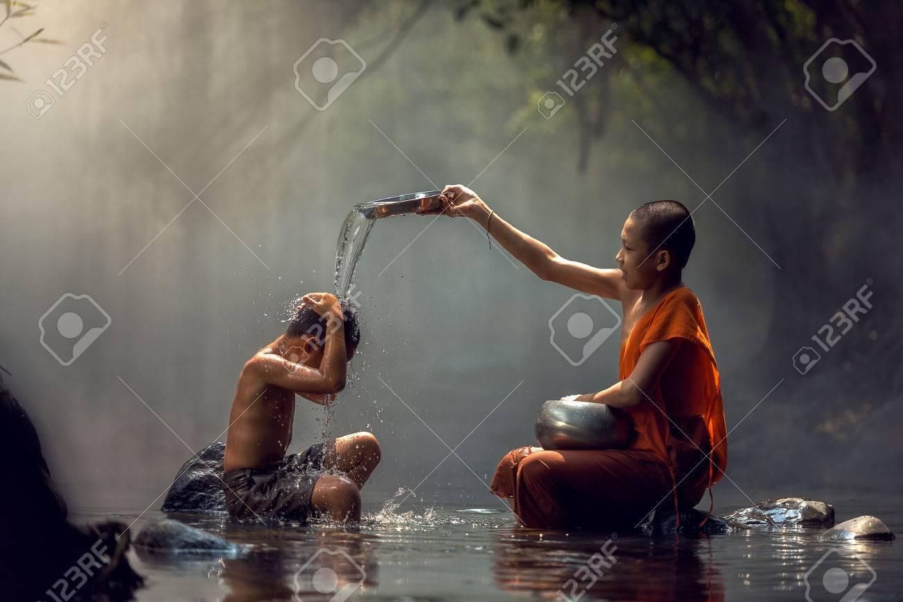 Little monk and child taking a bath at waterfall, Nong Khai, Thailand. - 60343361