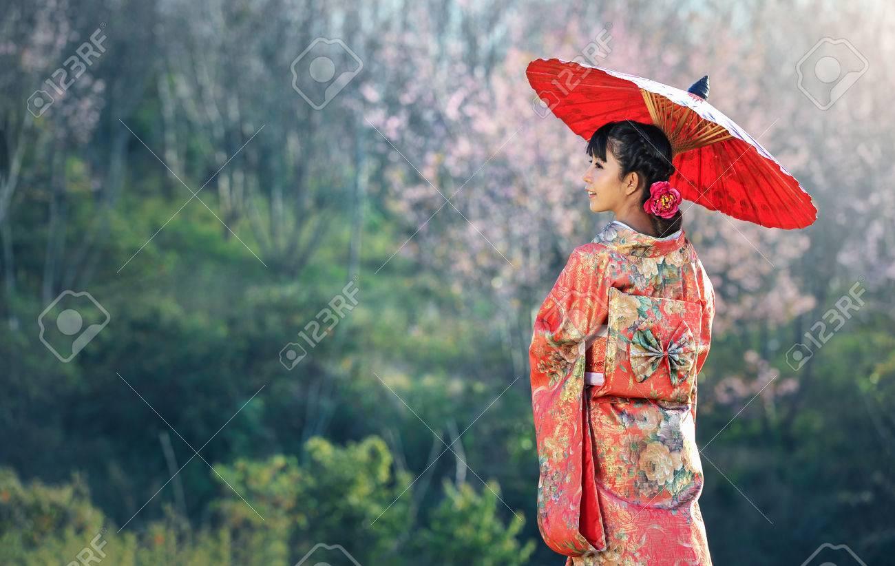 Asian woman wearing traditional japanese kimono, sakura background - 75553096