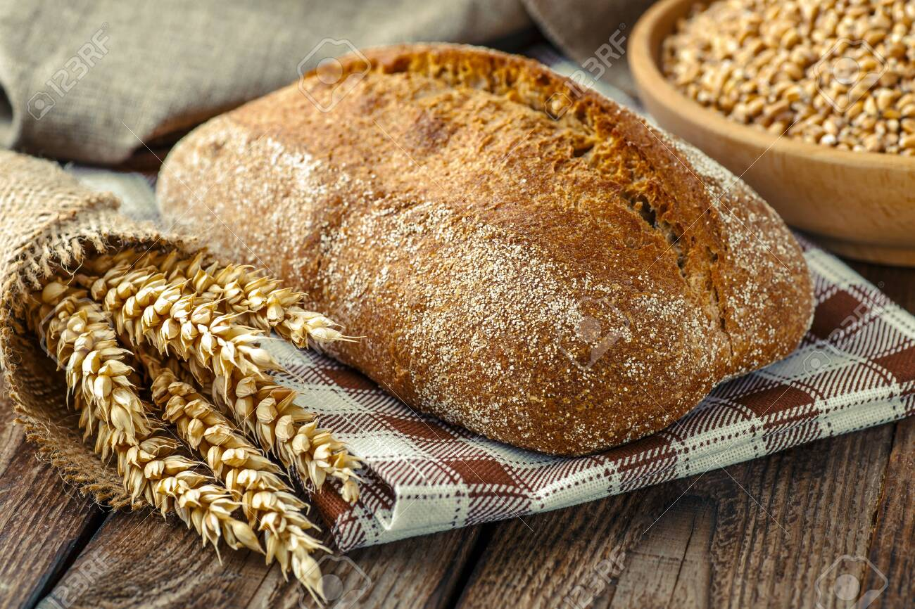 loaf of bread on wooden background, food closeup.Fresh homemade bread.French bread. Bread at leaven. Unleavened bread.Ciabatta bread. - 121591986