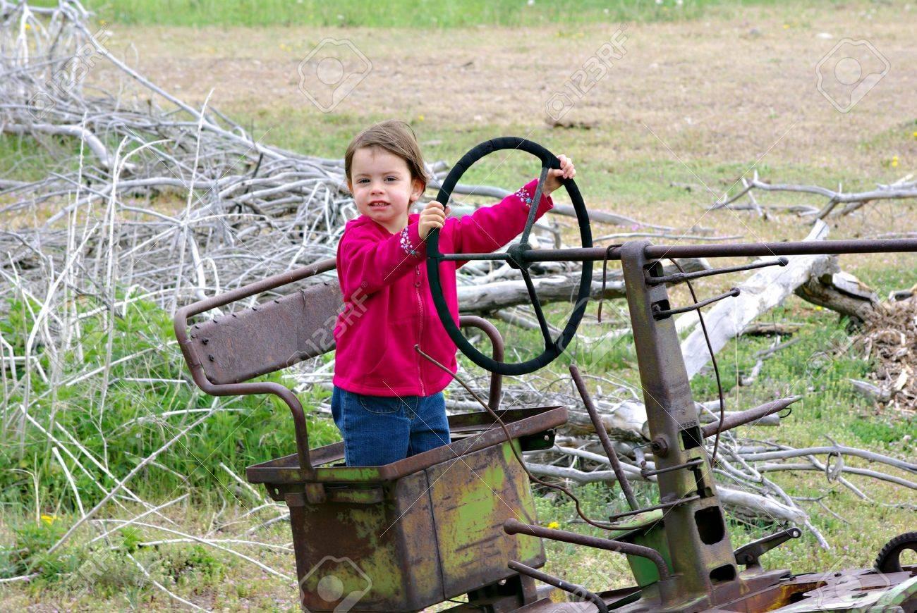 Una niña de pie en el asiento de un viejo tractor Foto de archivo - 5104920