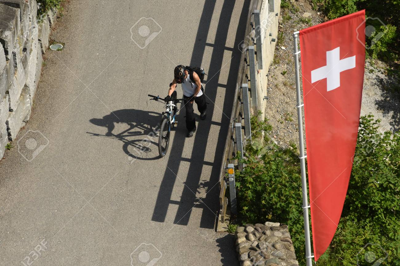 Man with bicycle and flags of Switzerland, top view from Uetliberg