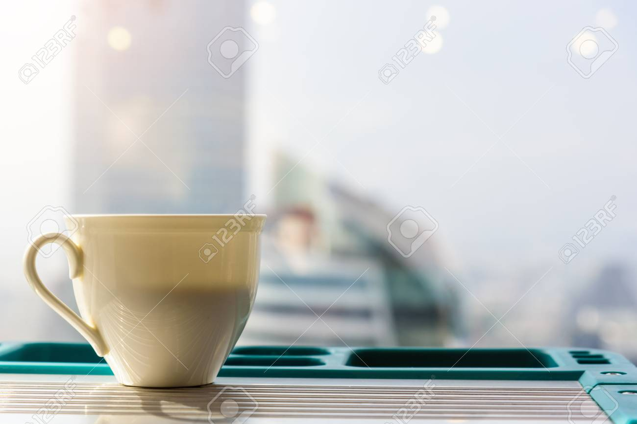 white coffee mug put on the table and have a back view or backgorund