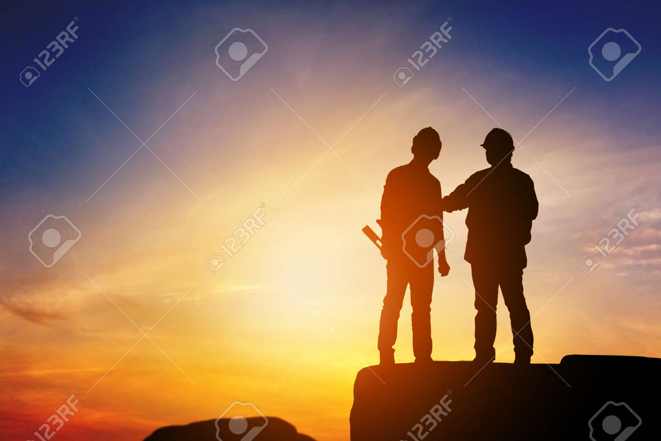 Silhouette of Engineer and worker standing on stone thinking of project sunset in evening time. - 159163395