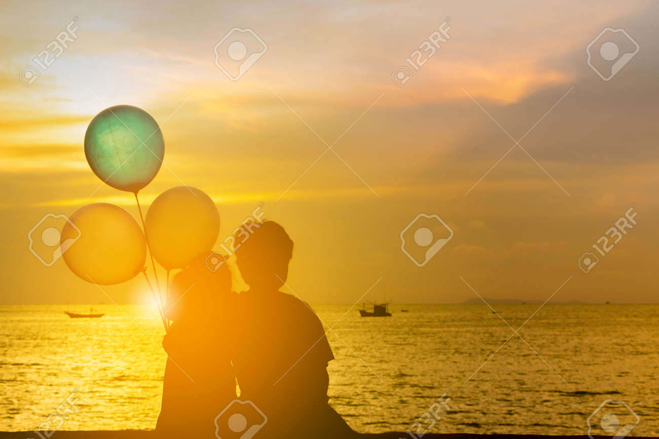 Silhouette of brother and sister sitting on the beach watching sunset with balloon in hand. - 159209127