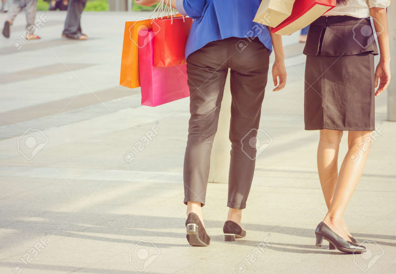 Close-up of young woman carrying shopping bags while walking along the street. Happy Life Style Concept. - 159218681