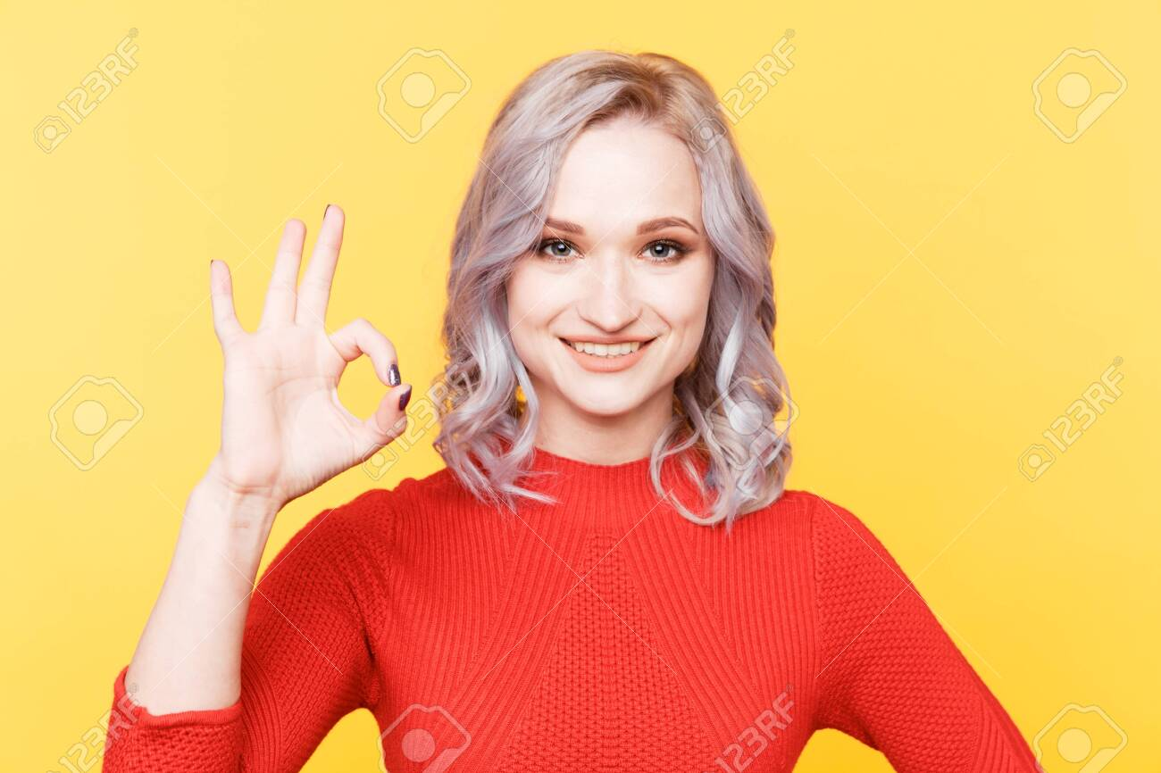Blond curly hair woman showing ok getsure isolated in the yellow studio. - 131882710
