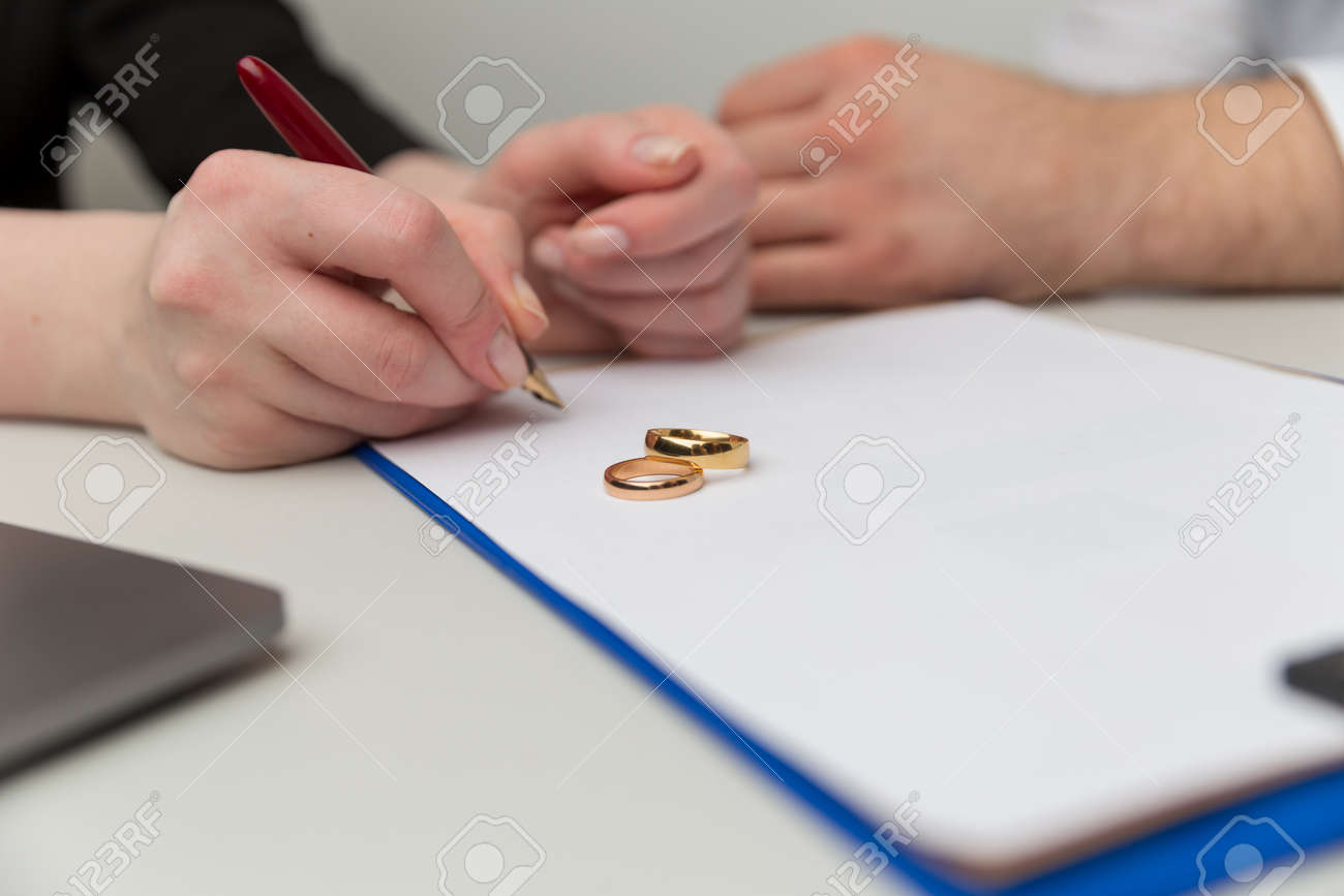 Prenuptial agreement concept. Man and woman signing notary document together. - 165753582