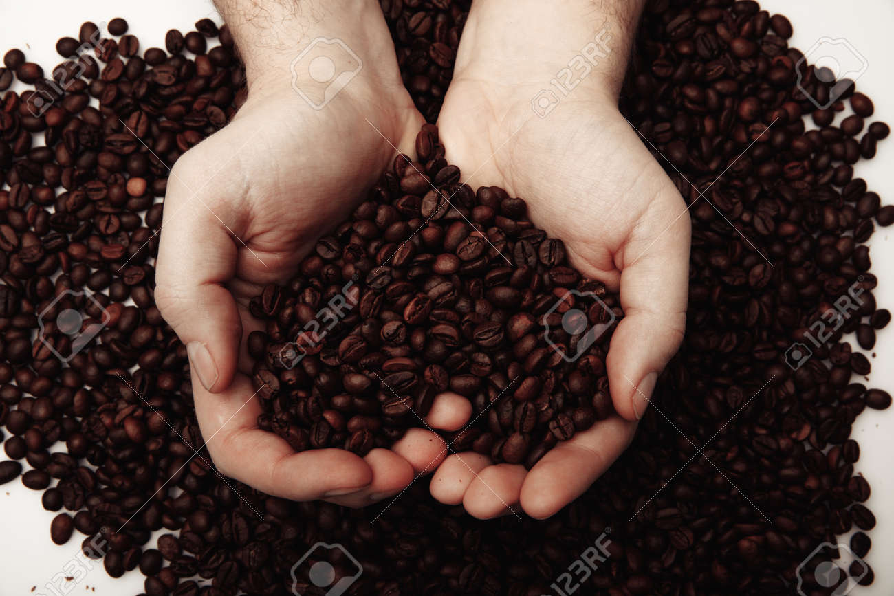 Coffee beans in man palms in form of a heart on coffee background - 169819175