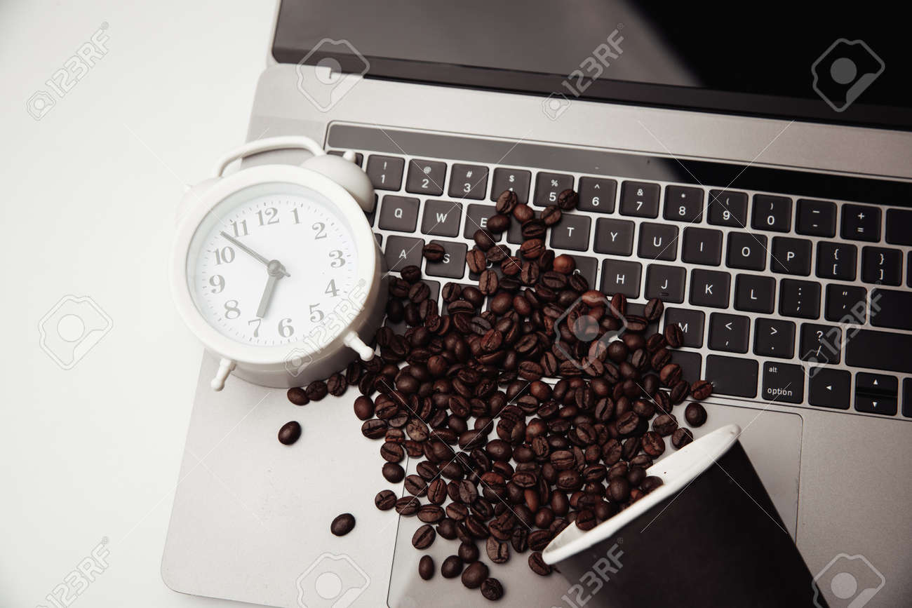 A cup of coffee on keyboard, alarm clock and coffee beans. Top view - 169819536