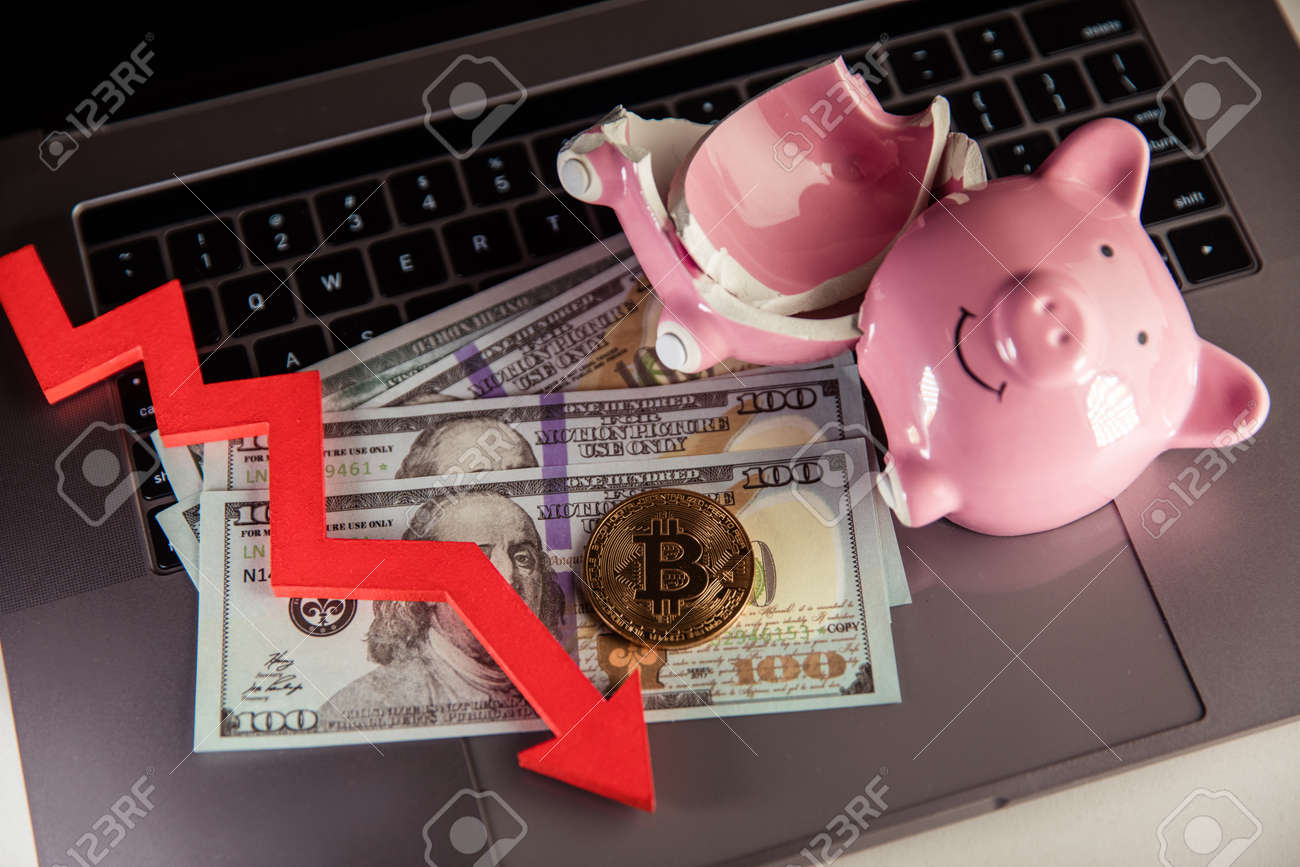 Bitcoin, broken piggy bnak and arrow down close-up. Cryptocurrency and investment concept. - 169819671
