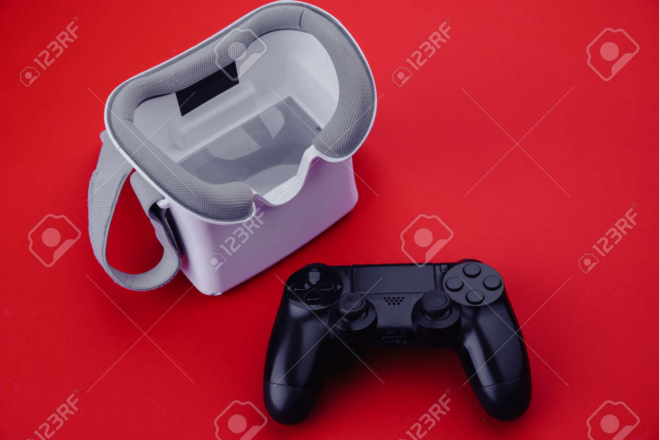 Gaming concept. VR virtual reality glasses with gamepad on red background - 169819669