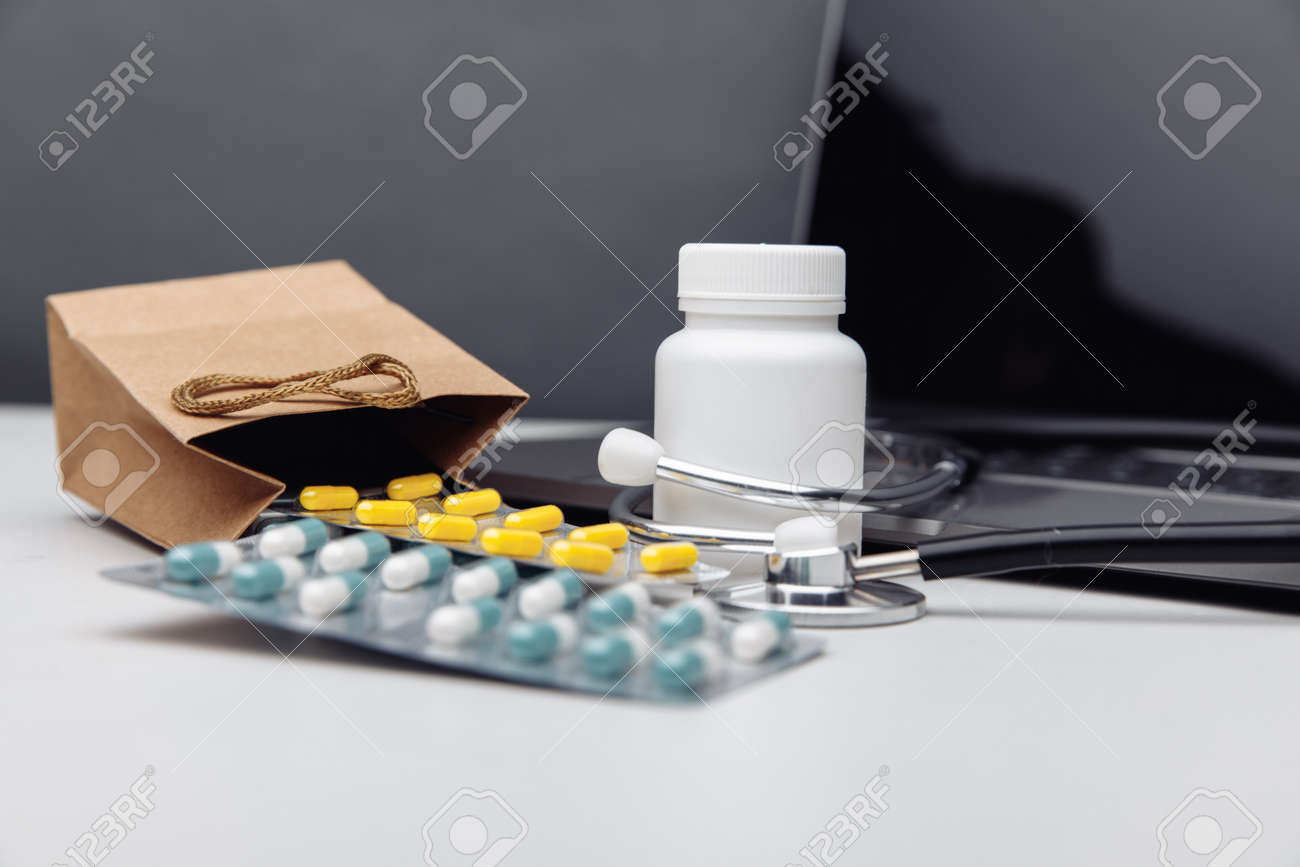 Online pharmacy shopping concept. Laptop and paper bags filled with assorted prescription medicines - 169820263