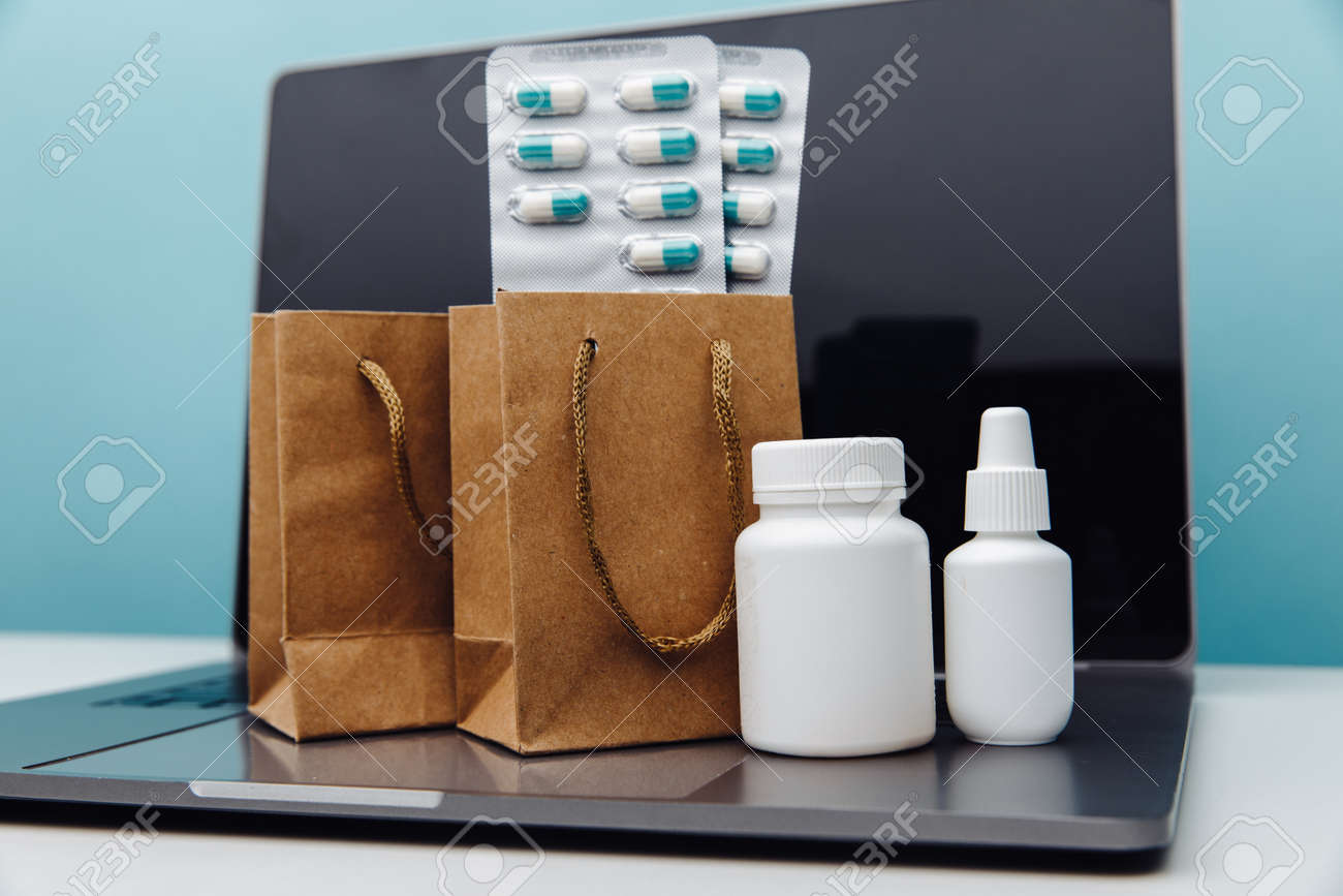 Online delivery and shopping concept. Paper bags with prescription drugs and pills and conteiners on laptop on blue background - 169820276