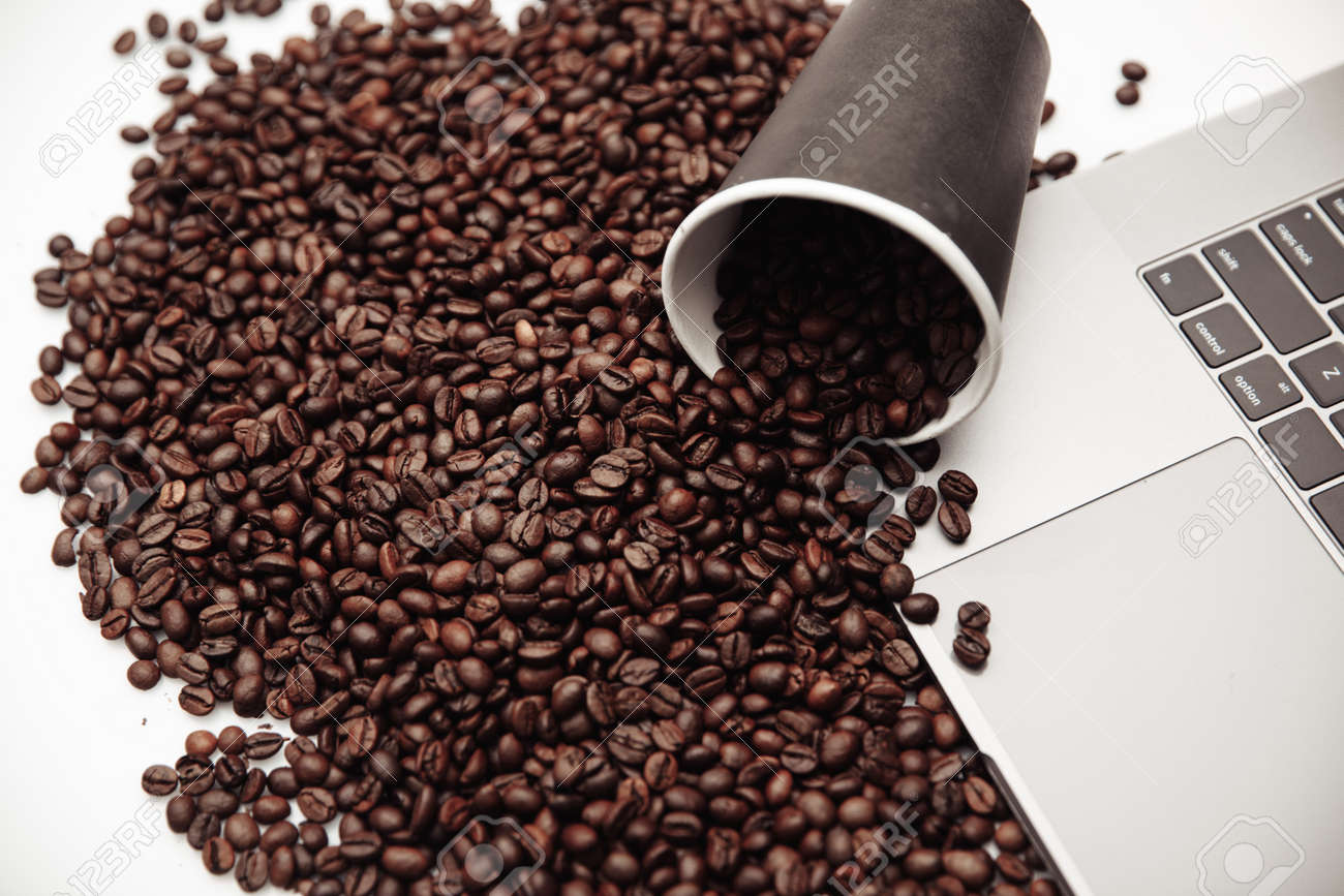 A cup of coffee on keyboard and coffee beans - 169820850