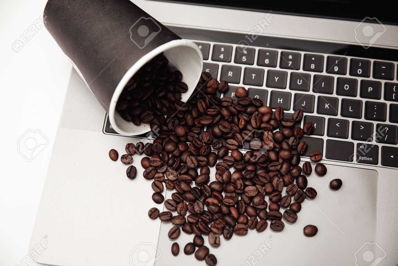 Paper cup and coffee beans on keyboard at the white desk - 169820851