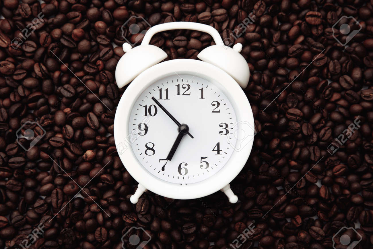 Alarm clock on coffee bean background. Morning with cup of coffee - 169820853