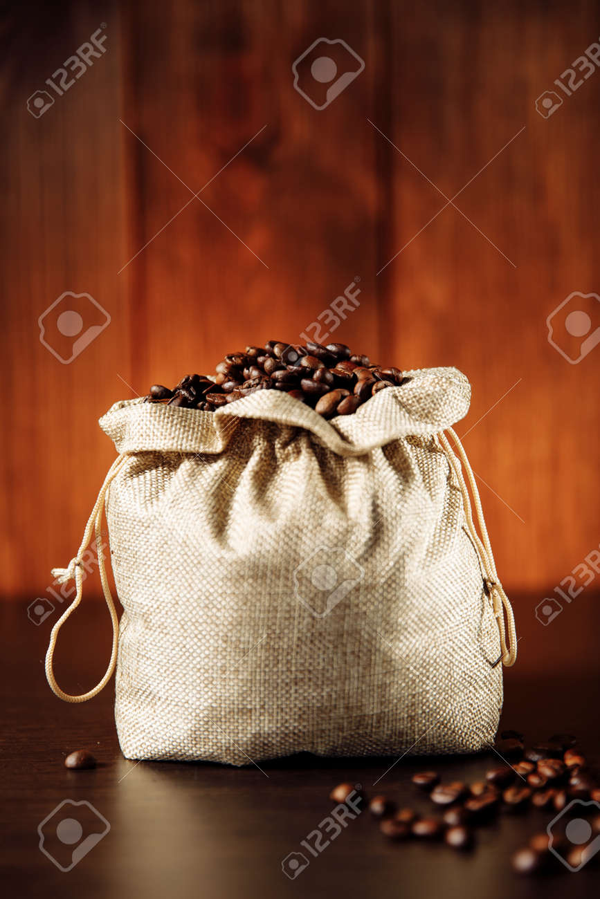 Roasted coffee beans in the bag on wooden background. Vertical image - 169820854