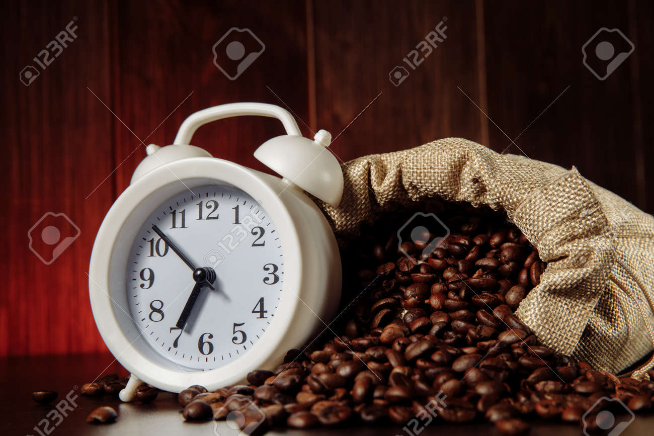 A white alarm clock and coffee beans in a sack bag close-up - 169820856