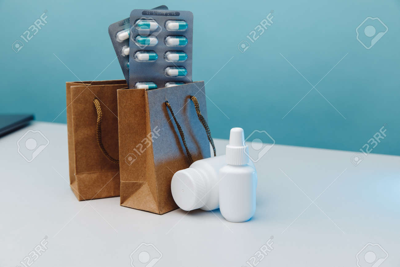 Online shopping theme. Paper bags with medical white containers and pills on blue background - 171975046