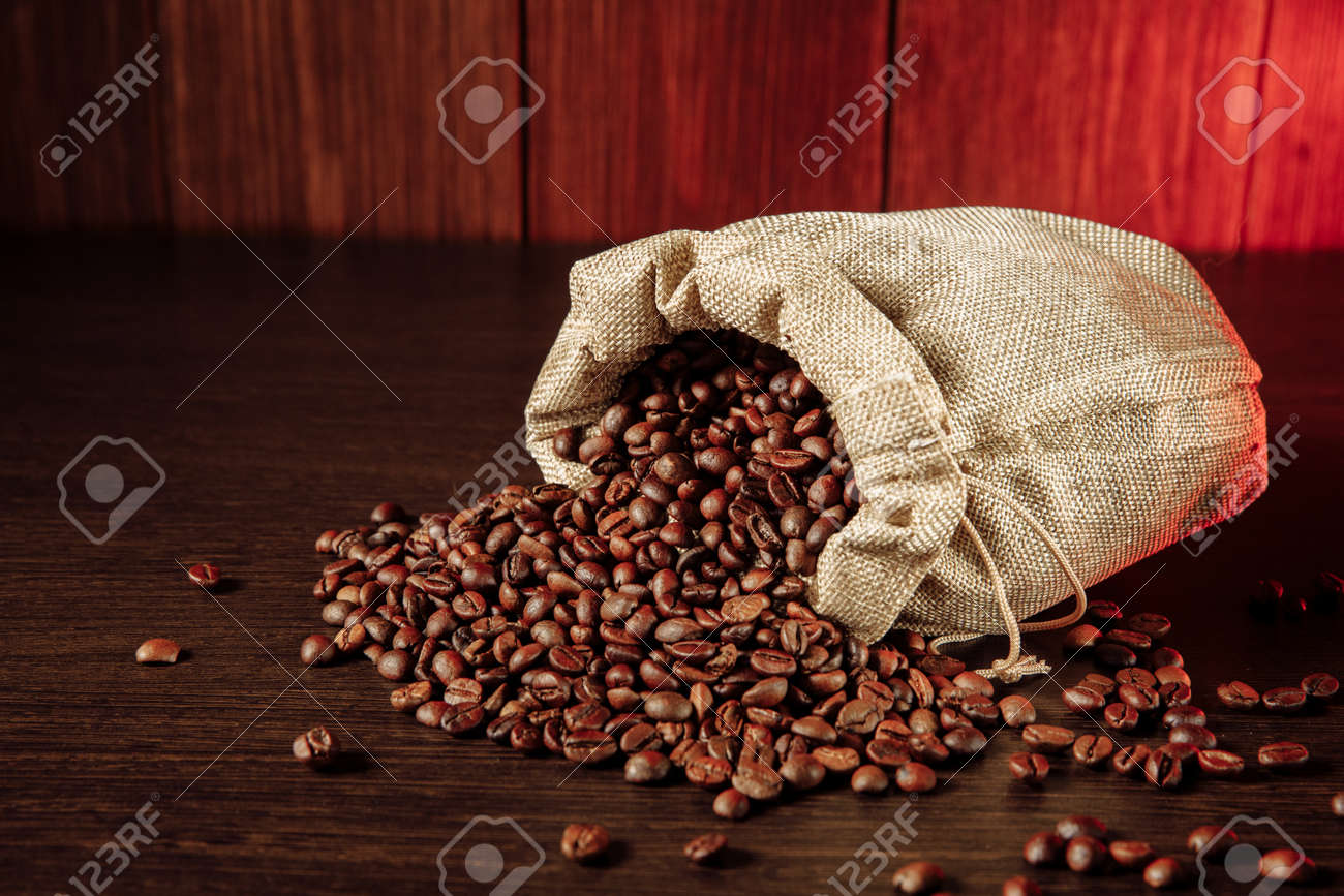 Brown coffee beans scattered of the bag on table - 171975048