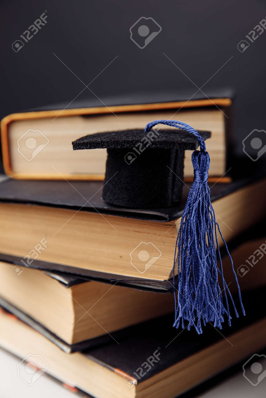 Mini graduation hat on stack of books. Vertical image - 171975049