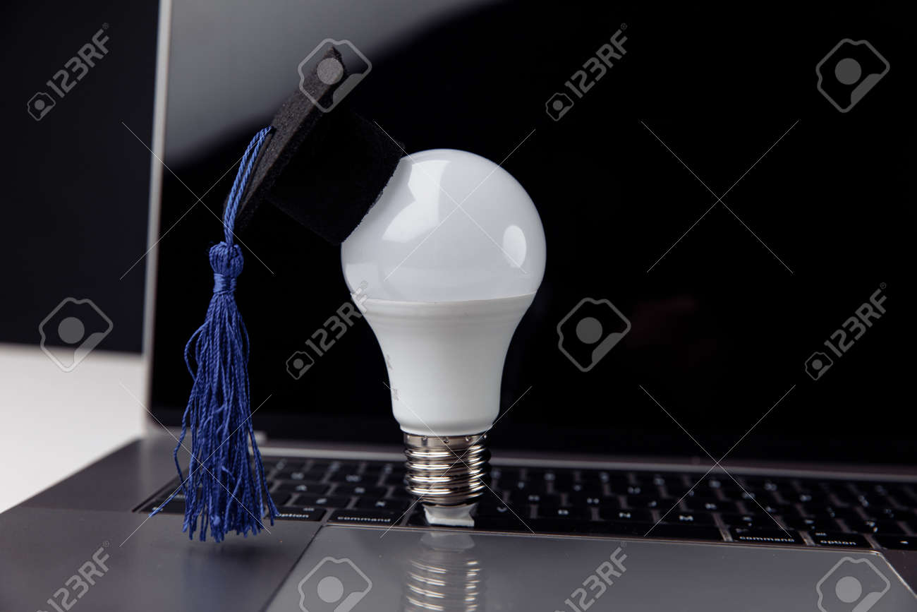 Graduation hat on light bulb with laptop on table. Education concept - 171967105