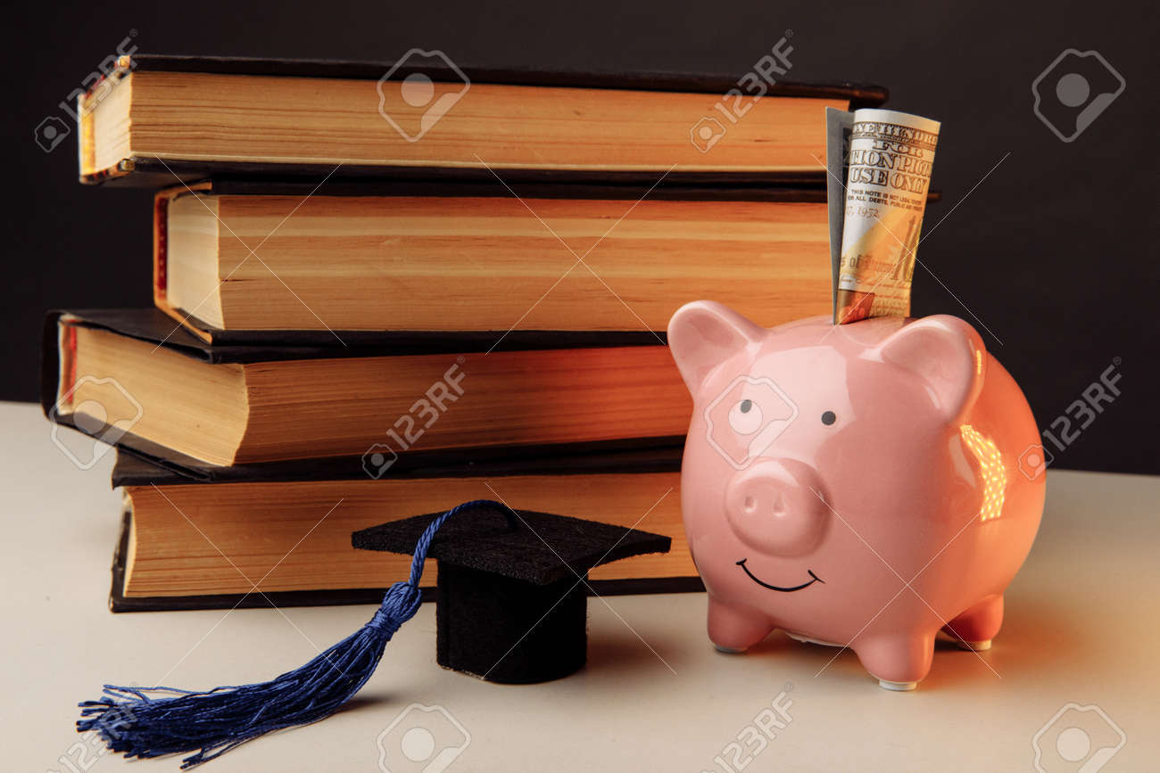 Ceramic moneybox with stack of books. College, graduate, education concept - 171966821